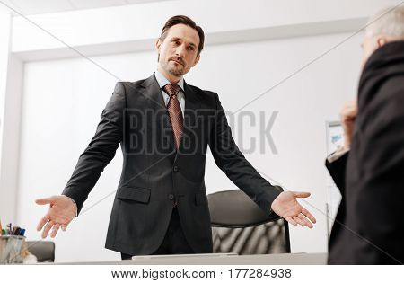 Your time is over. Confident serious proficient HR manager standing in the office while expressing disappointment and dismissing the employee