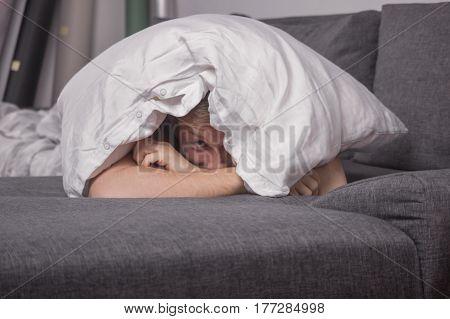 One Young Man Peeking Beneath Pillow