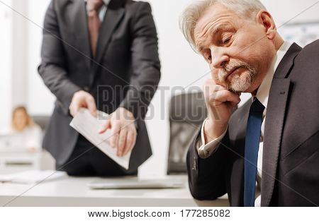 Full of disinterest. Indifferent upset aged employer sitting in the office and expressing indifference while listening to the report of the employee