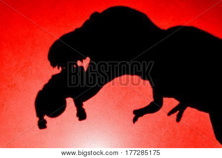 shadow of tyrannosaurus biting a body on wall in red close up no logo or trademark