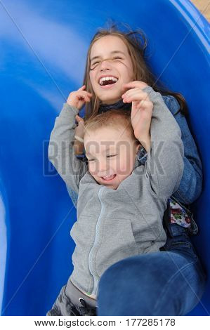 Smiling girl and boy having fun on children's slide. Outdoor portrait of a cute children at playground