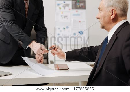 Determinative moment for the company . Hesitant bearded aged employer sitting in the office and expressing concentration while signing the document and having conversation with employee
