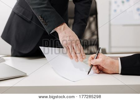Crucial decision. Confident serious experienced businessman sitting in the office and expressing concentration while signing the document