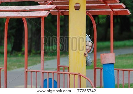 Little boy peeping on the children's playground.
