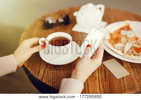 Girl holding smartphone with empty screen, texting, eating pizza and drinking a cup of tea at the cafe, relaxing home atmosphere. Shallow depth of field