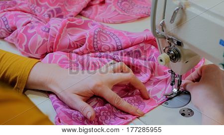 Professional tailor, fashion designer sewing clothes with sewing machine at atelier. Fashion and tailoring concept