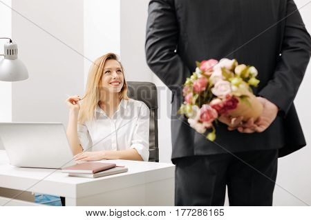 Romantic surprise for you. Gallant involved charismatic employee holding the bouquet behind his back while standing near the colleague and having conversation