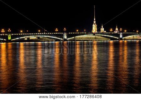 Night of St. Petersburg on the Neva, Peter and Paul fortress over the bridge and light reflections in the water