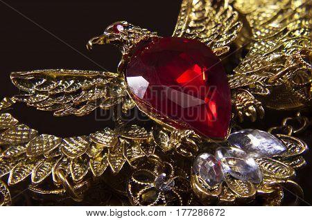 Golden eagle jewel pendant with ruby stone closeup photo.