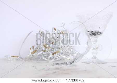 Elegant vintage etched cocktail glasses with silver stars spilling out and silver streamers. Open space for copy.