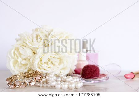 Elegantly styled make up, jewelry and flowers with open space for copy.