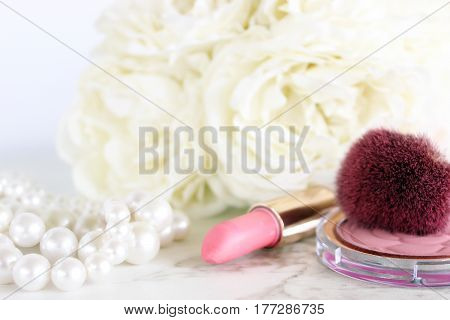 Close up of pink make up items, pearls with white flower bouquet in the background. Open space for copy.