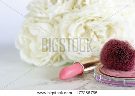 Close up of pink make up items, with white flower bouquet in the background. Open space for copy.