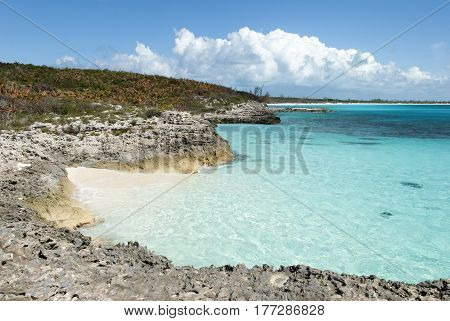 The rocky coastline with a tiny beach trapped in between of uninhabited island Half Moon Cay (Bahamas).