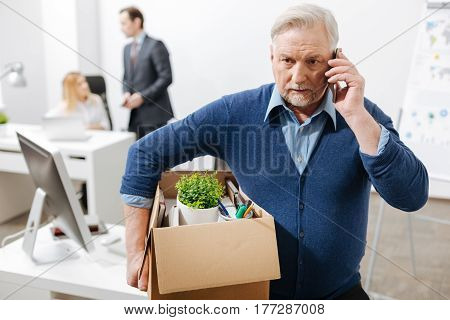 Bad news. Fired sad aged employee standing and holding the box with his belongings while leaving the office and having conversation on the phone