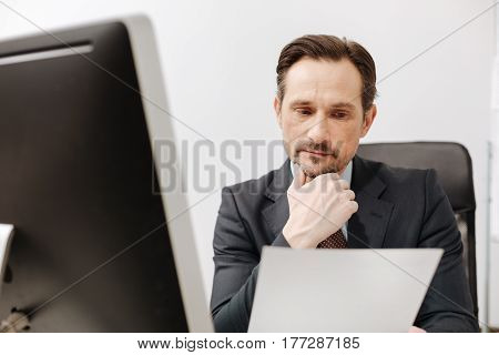 Reading attentively. Charming attentive involved office manager sitting in the office while expressing positivity and reading documents