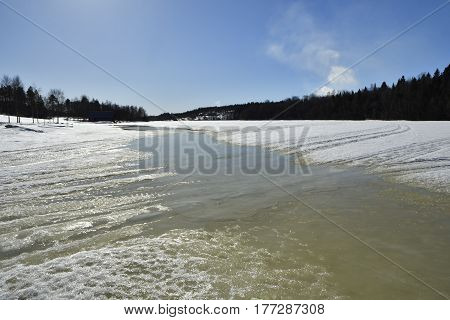 Melting sea ice in spring sun with forest and blue skypicture from the North of Sweden.