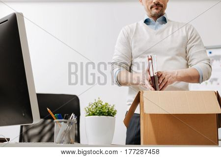 Searching the solution . Fired involved depressed employee standing and packing the box with his personal stuff while leaving the office and expressing sadness