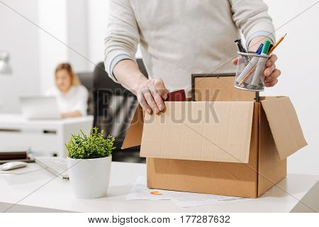 Taking a gap. Concentrated involved melancholy employee standing and packing the box with his belongings while leaving the company and expressing sadness