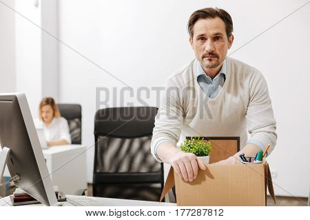 My career collapse . Depressed puzzled sad employee sitting and holding the box with his belongings while expressing sadness