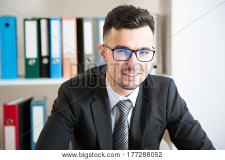 Happy young businessman portrait in office