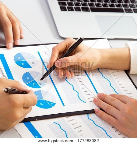 Close-up of businesswoman explaining a financial plan to colleague