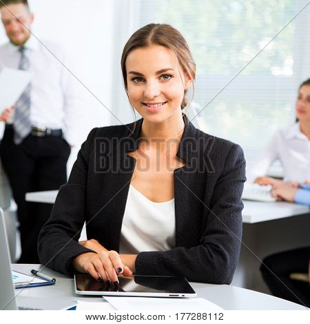 Beautiful young businesswoman with colleagues on the background