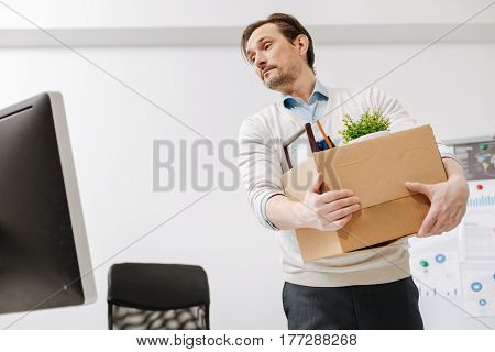 Leaving my previous life. Fired melancholy upset employee standing and carrying the box with his personal documents while expressing sorrow