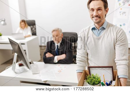 Never give up. Fired smiling positive employee standing and carrying the box with his personal documents while expressing positivity and leaving the company