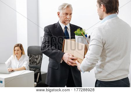 Very stressful day. Aged serious confident employer standing and giving the box to the employee while firing man from the company