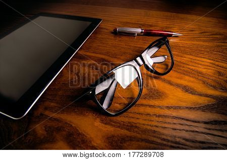 Glasses with pen and tablet on a wooden natural table. Home office. Concept of work in a office and accessories.