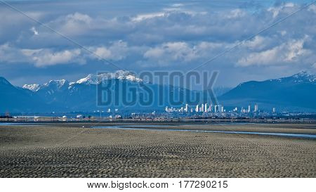City skyline snowy mountains and low tide on Boundary Bay. Great Vancouver. Tsawwassen. British Columbia, Canada.