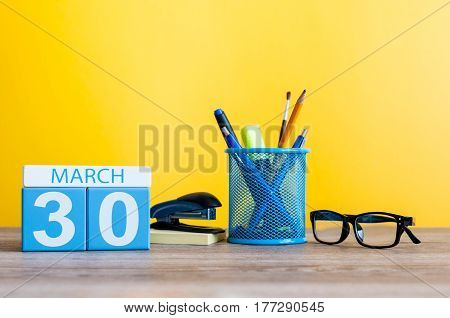 March 30th. Day 30 of month, calendar on light yellow background, workplace with office suplies. Spring time, empty space for text.
