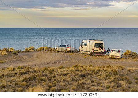 SANTA CRUZ, ARGENTINA, MARCH - 2016 - Group of people with cars enjoying the view of ocean at coast in Santa Cruz province Argentina