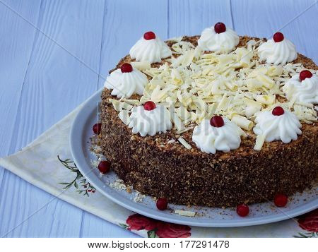 Chocolate Cake Decorated With Rosettes Of Cream And Berries On A Wooden Background.