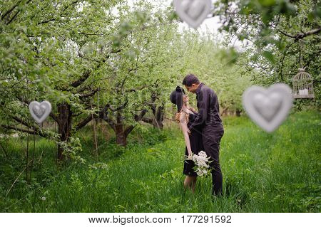 Wonderful love story in photos. Pretty pair in green fruit garden hugging and kissing