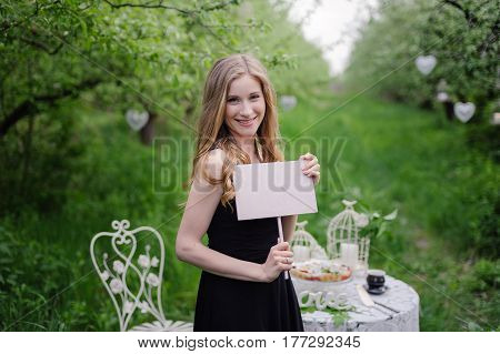 Wonderful love story in photos. Portrait of girl in black beautiful dress with background of green garden, with Bride label