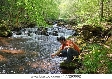 Man drinking water from the river. Clean unpolluted water in the river,