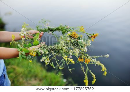 Wreath of wild flowers in children's hands close-up on the background of the river