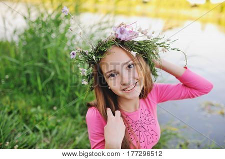 Baby girl in wreath of wild flowers and background of nature. Mid-summer day. Easter. Ivan Kupala