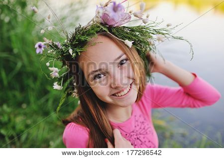 Baby girl with a big wreath of wild flowers on her head against a background of blooming nature