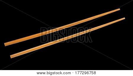 Two wooden chopsticks isolated on black background