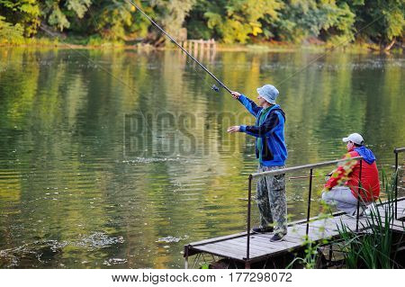 Two fishermen with fishing rods catching fish in the river standing on the pier bridge
