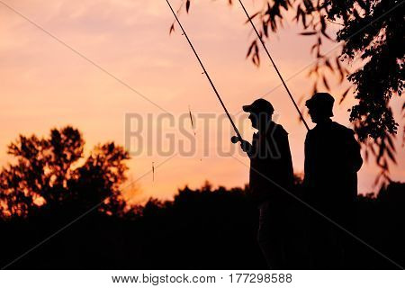 Silhouettes of two fishermen at sunset with fishing rods on the background of nature and pink sky. Fishing