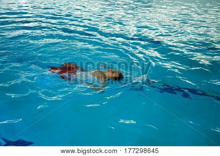 Young boy floating on his back in a swimming pool.
