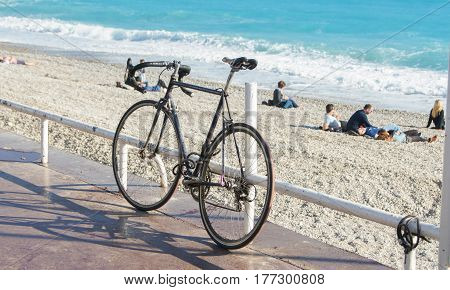 Nice, France - 25 February, Bicycle on the leash, 25 February, 2017. People and tourists having a rest on the Cote d'Azur.