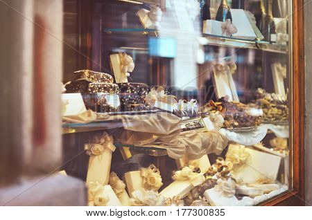 Rich variety of chocolates candies and biscuits with a gift box in display window of italian pastry shop at the street of Florence city