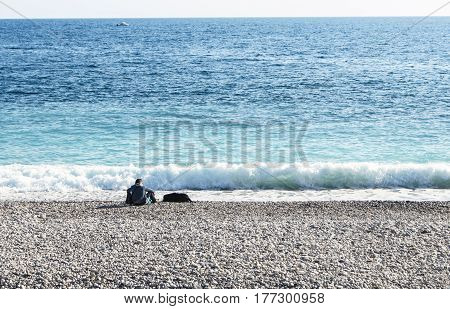 Nice, France - 25 February, A man with a dog by the water, 25 February, 2017. People and tourists having a rest on the Cote d'Azur.