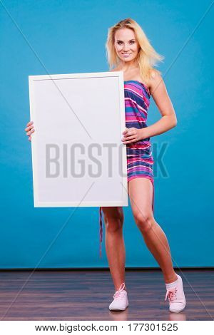 Presenting advertisement concept. Happy positive blonde woman wearing colorful short dress holding blank white board