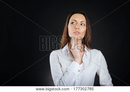 Let me think. Enigmatical brunette female wearing white shirt looking sideways while standing isolated on black
